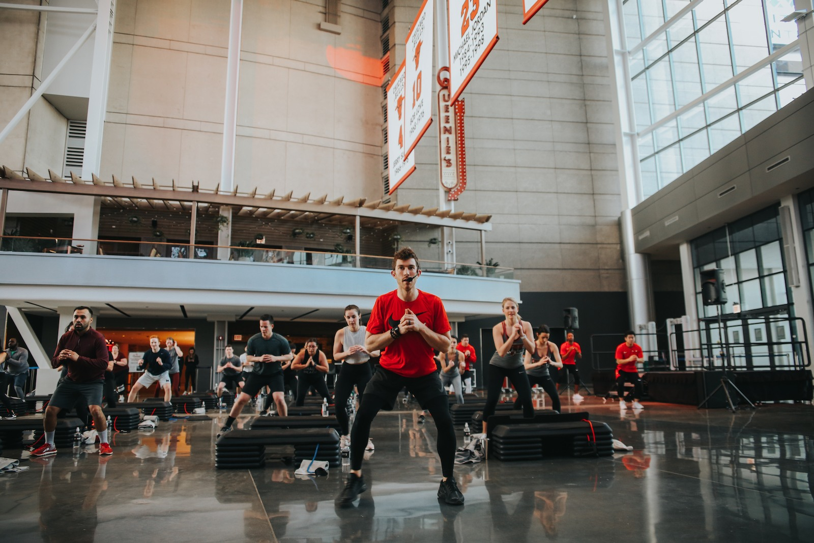 Barry's Bootcamp instructor in red t-shirt leading class in the United Center Atrium in Chicago