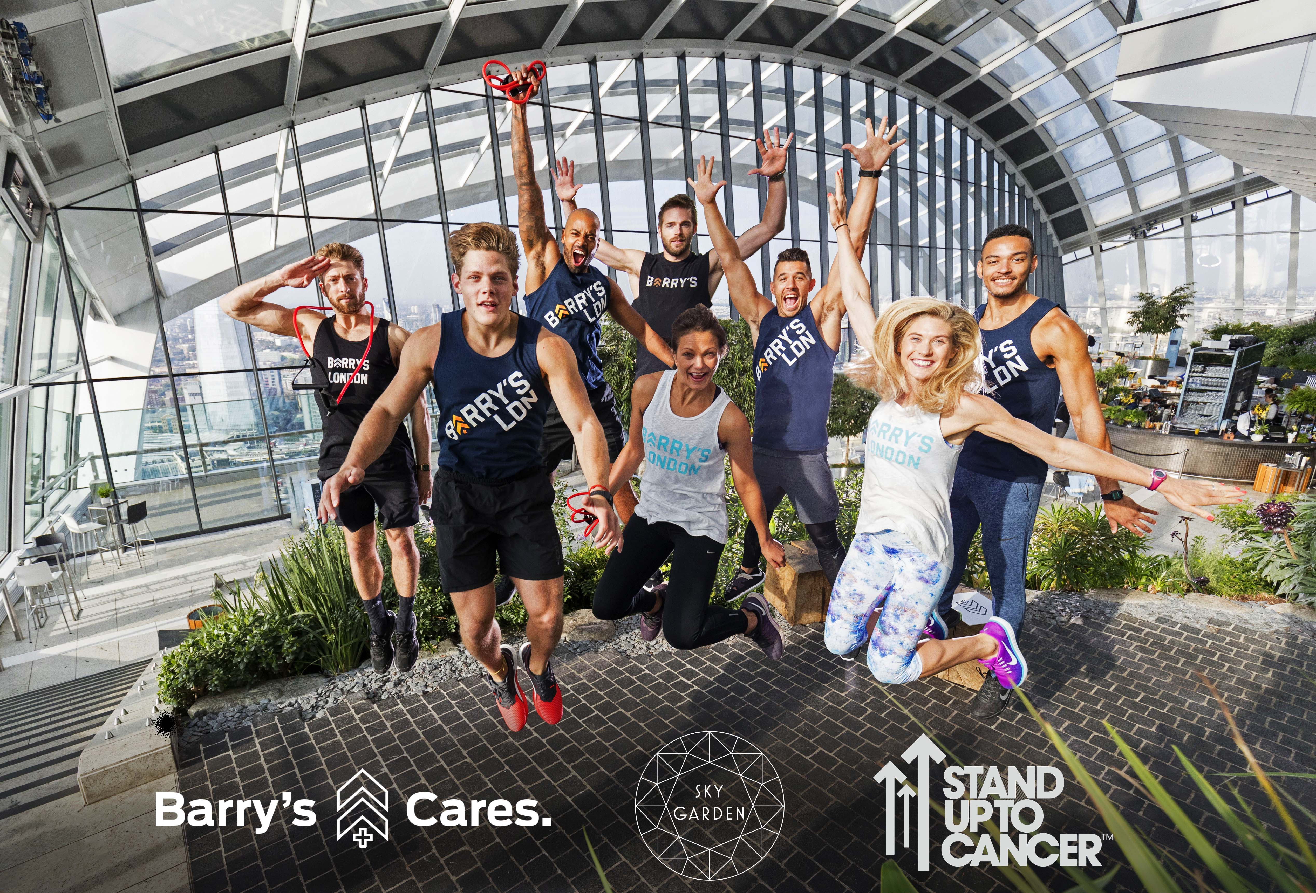 Barry's Bootcamp instructors jumping in London Sky Garden with Barry's Cares, Sky Garden, and Stand up to Cancer logos
