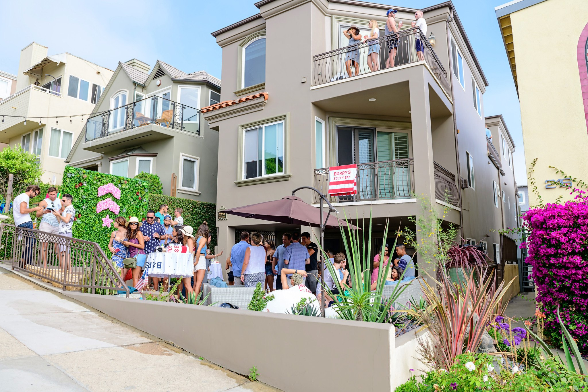 Gathering at Barry's Beach House event as seen from the street with pink floral logo and living wall visible on patio