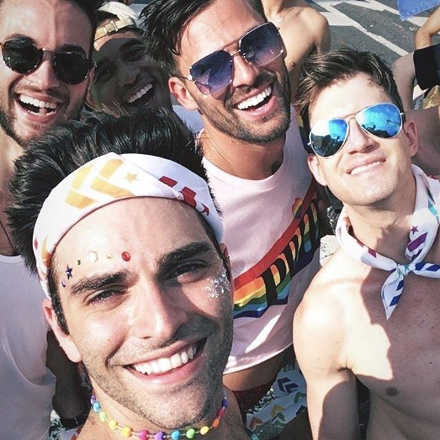 Group of young men wearing rainbow Barry's Bootcamp bandanas and smiling in the sun on the street