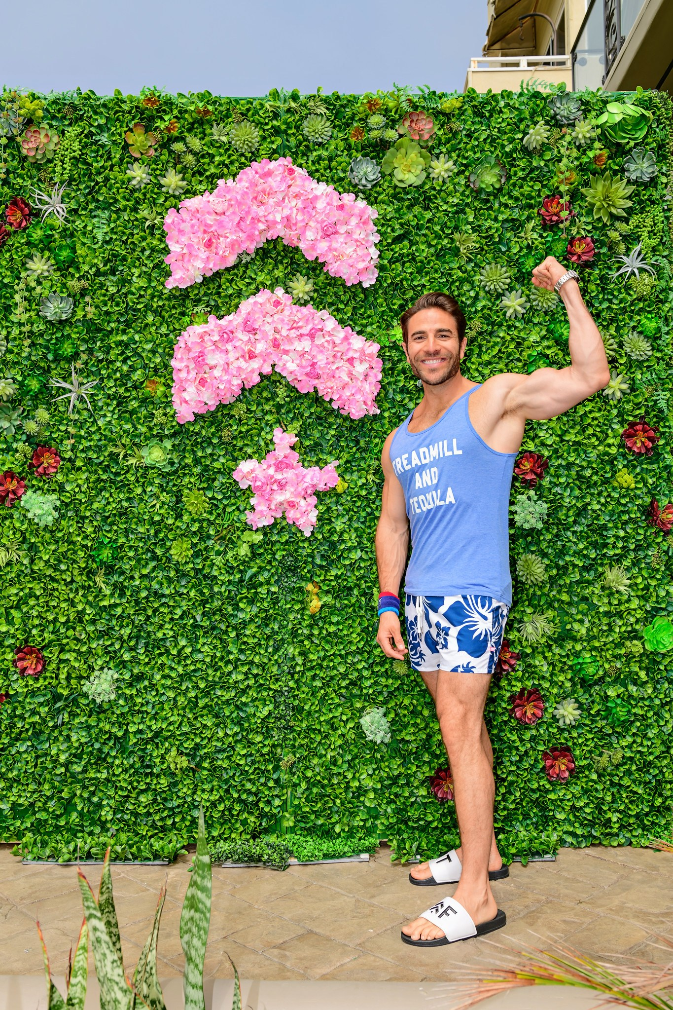 Man in like blue tank top and blue floral shorts flexing in front of pink floral Barry's Bootcamp logo and living wall