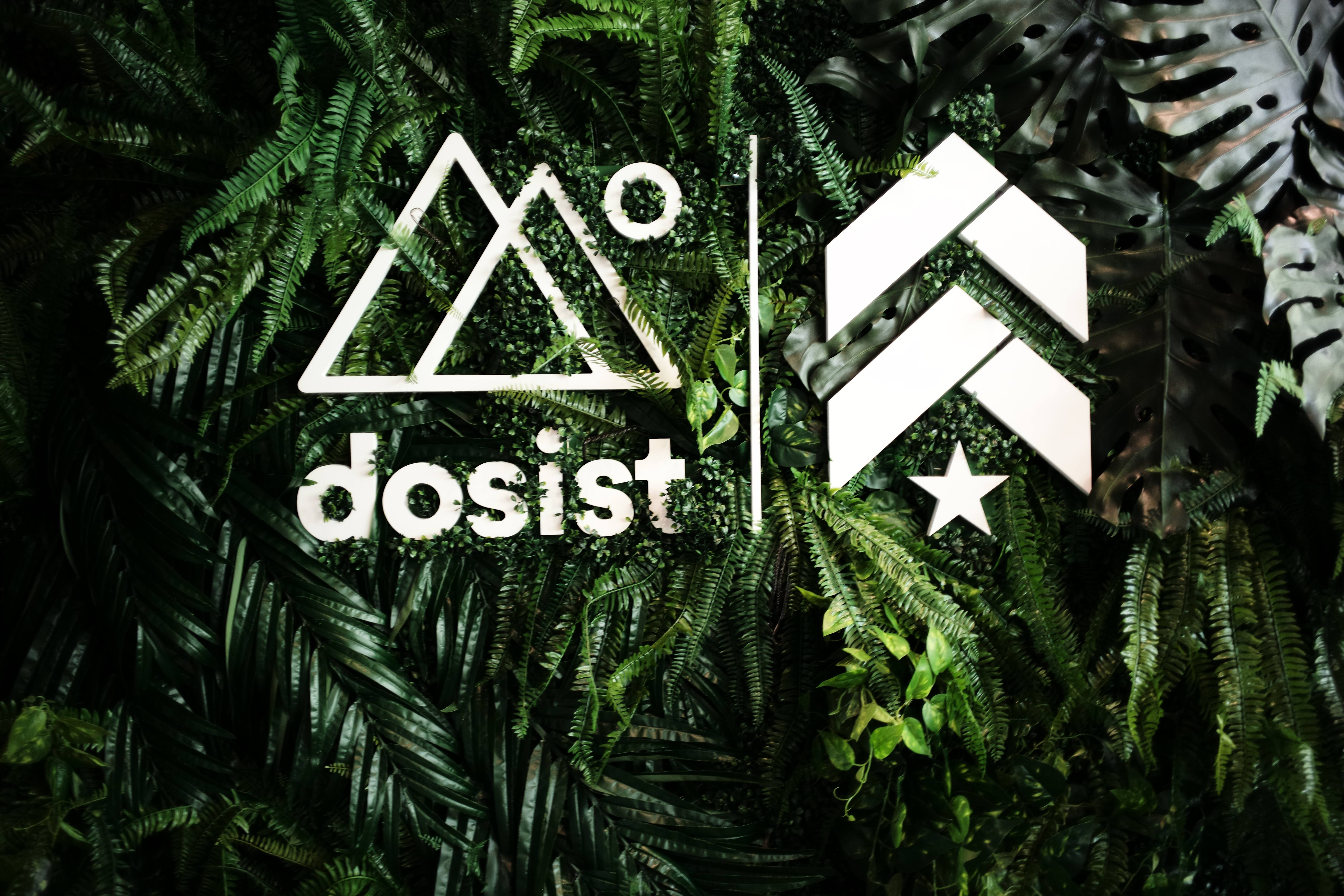 Dosist double triangle and Barry's Bootcamp upward arrows and star logos on wall of greenery