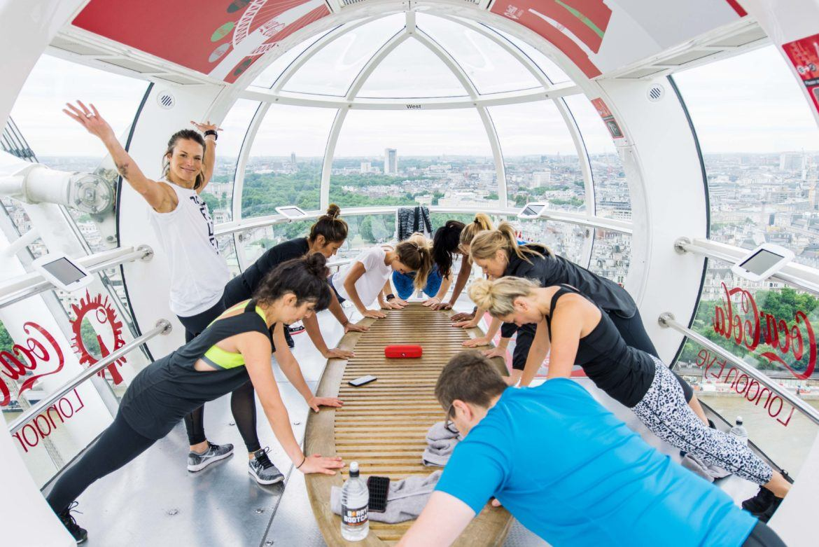 Barry's Bootcamp instructor looking proud as small group does incline pushups inside a London Eye pod