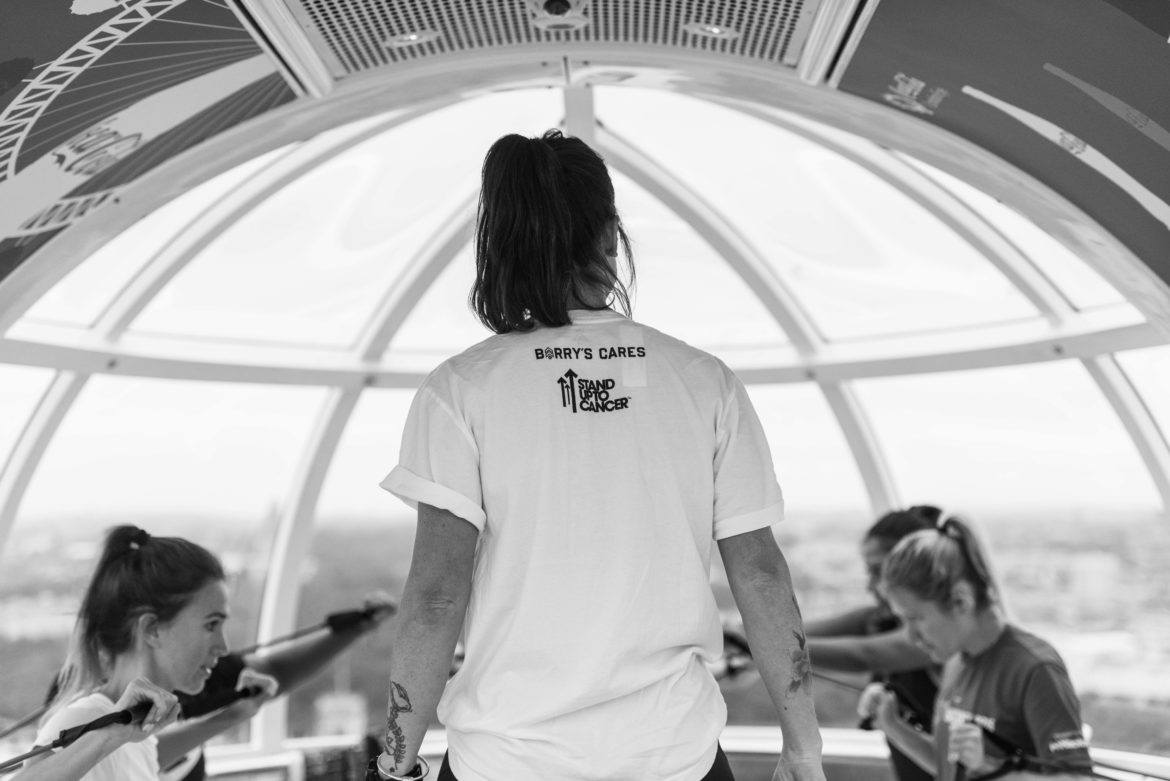 Back of female Barry's Bootcamp instructor wearing white t-shirt as she looks at the class inside the London Eye