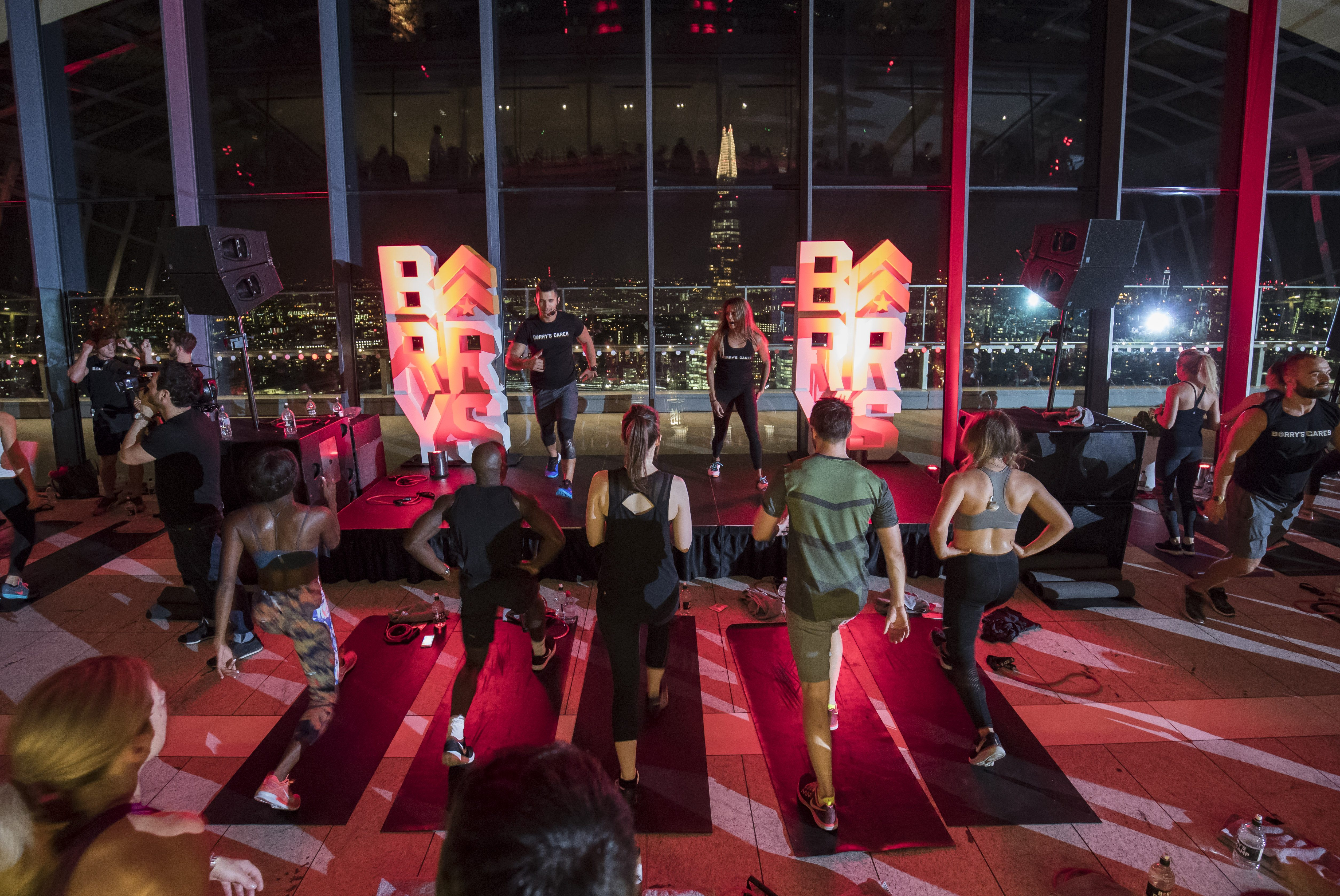 Barry's Bootcamp London Sky Garden participants following instructors doing fitness moves on stage