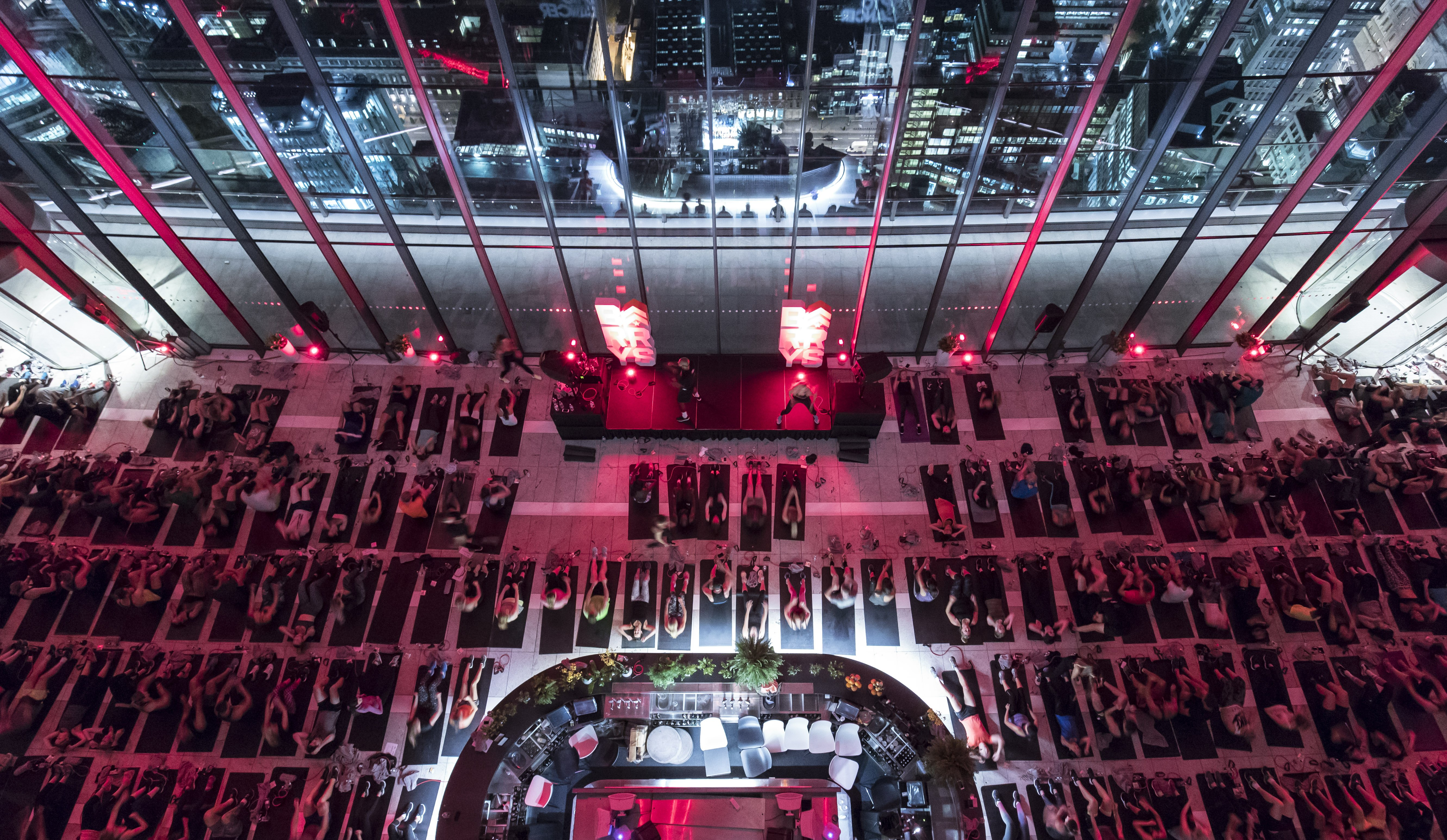 Overhead view of Barry's Bootcamp class at the London Sky Garden in front of red lights and large glass windows
