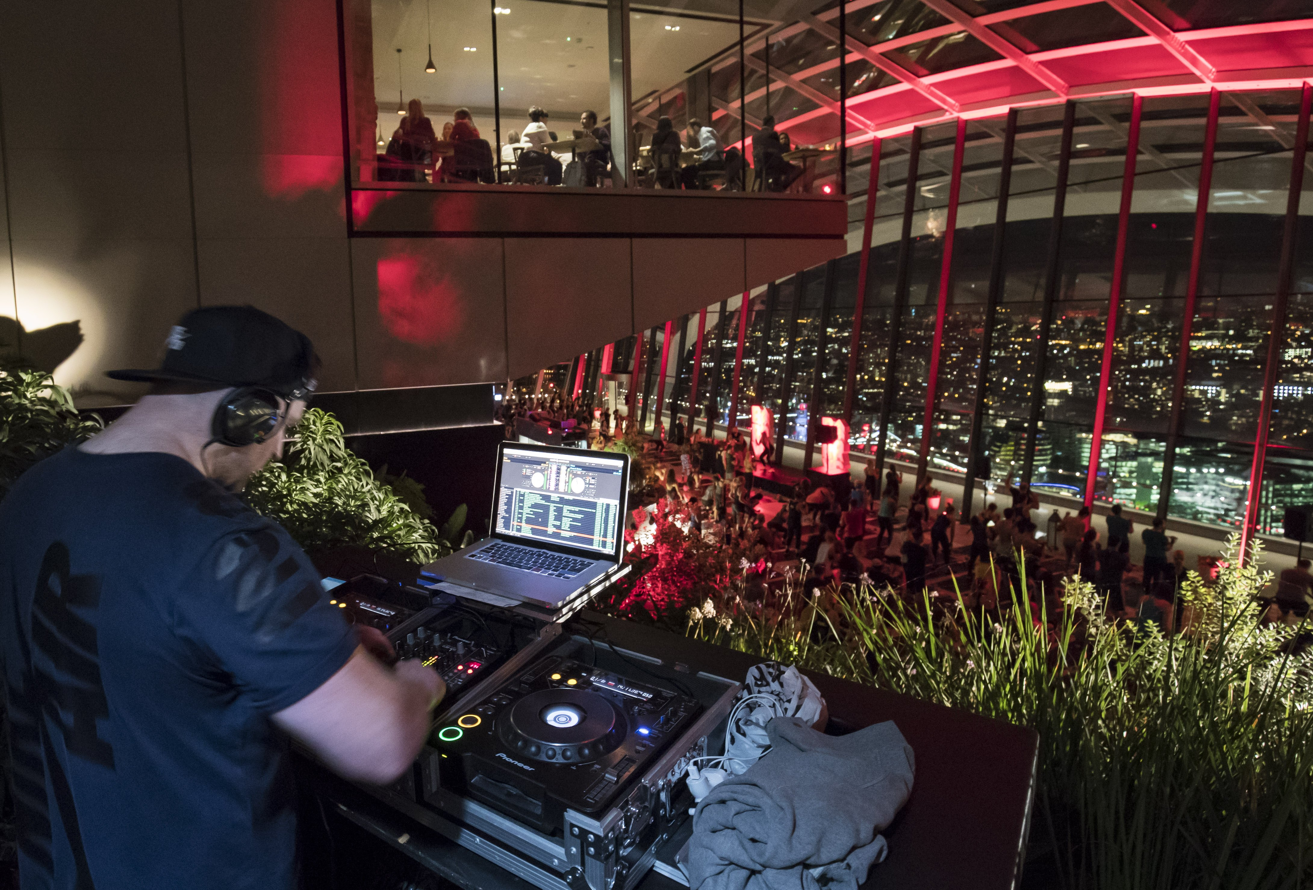 DJ overlooking Barry's Bootcamp nighttime fitness class in the London Sky Garden in front of large glass windows