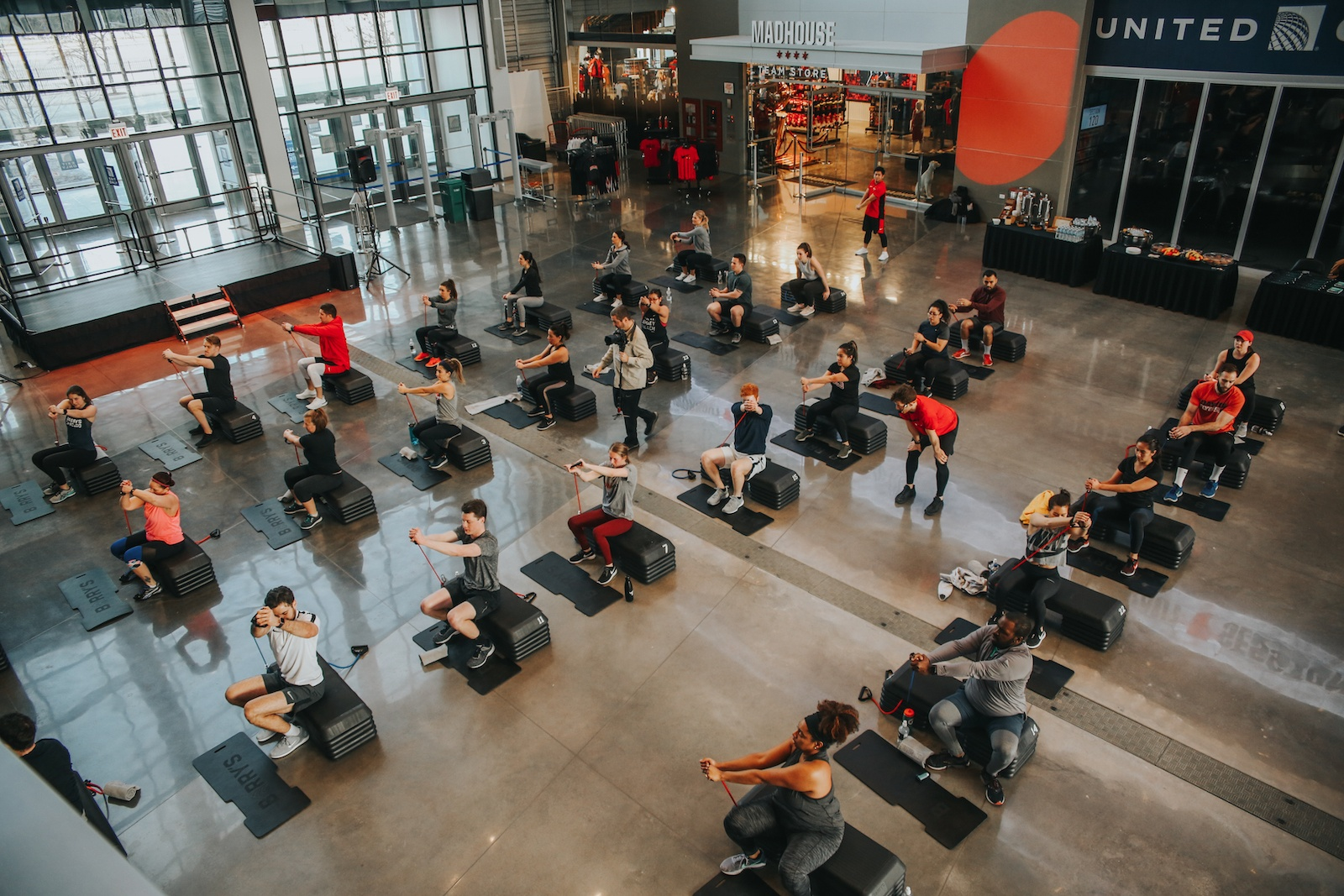 Barry's Bootcamp class in atrium of United Center in Chicago sitting on step up blocks while pulling resistance bands across their chests
